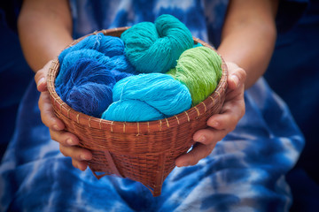 Close up woman's hand carry wicker basket with colourful yarns cotton. Image made selective focus.