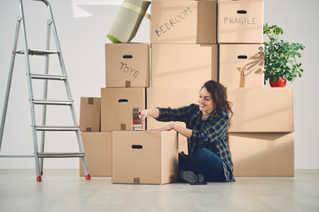 woman moving in new apartment taping boxes, packing, unpacking