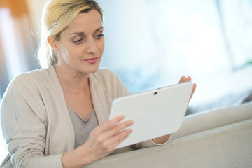 Blond woman at home connected with digital tablet