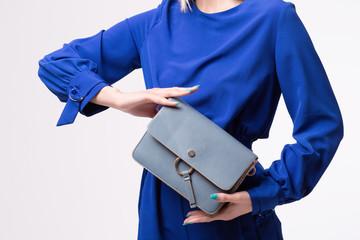 Elegant woman holding luxury handbag isolated on white background