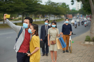 Air pollution in busy city center: young couple in protective masks taking selfie on smartphone while passers-by looking at camera with dissatisfied