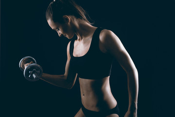Strong fit woman exercising with dumbbells