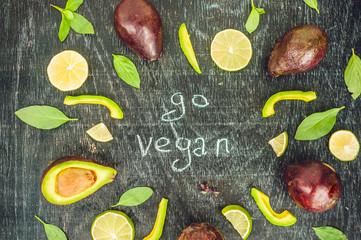 Go vegan concept with lettering. variety of fresh green organic vegetables lentils on dark background. Vegan food concept
