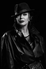Elegant fashionable woman wearing black coat and hat