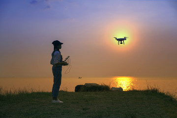 drone flying practice by girl on beach at sunset silhouette