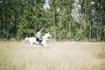 Happy brunette woman riding her white stallion, having fun at the summer field