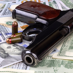 Pistol with bullets on the banknotes of American dollars, crime or corruption concept.