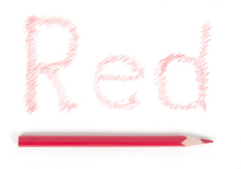 Word Red on a white paper and the red pencil
