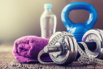 Fitness Equipment. Kettlebell  dumbbells towel water and measuring tape.