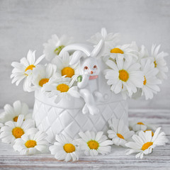 White daisies in a beautiful vase decorated with a bunny on the old wooden background.