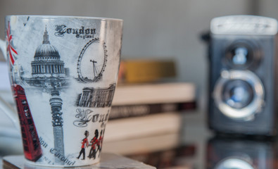 horizontal image london mug with books and film camera in background
