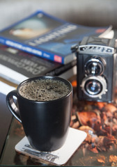 Coffee with film camera and pile of books