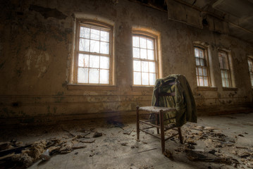 Old suit coat hanging on a chair in an abandoned room Wall mural