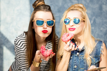 Playful women having fun with sweet donuts on the blue wall background
