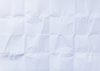White sheet of paper folded in sixteen, white background and texture.