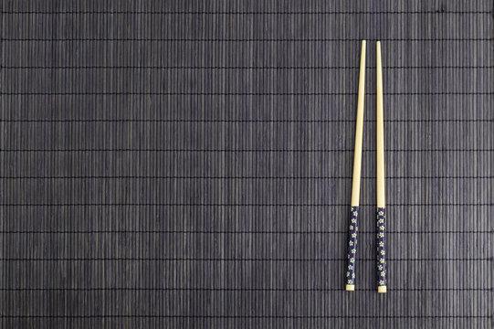 Wooden chopsticks on brown bamboo straw mat
