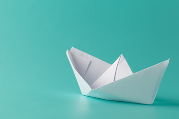paper boat on aquamarine background