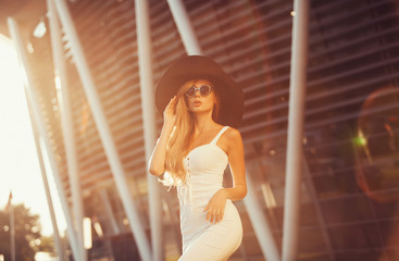 Beautiful woman in elegant hat and sunglasses posing outdoor. copy space
