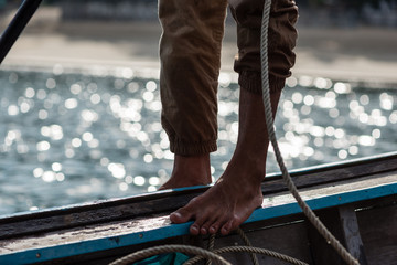 Closeup of legs and feet of sailor standing on railing of wooden boat, pulling in a rope