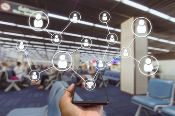 Hand using Smartphone and wifi icon social media connection concept at the airport on blurred background of passengers waiting bording at airport, color tone effect.