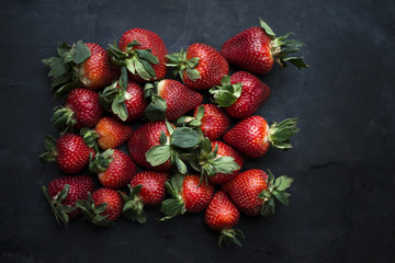 Overhead view of fresh strawberries on dark background
