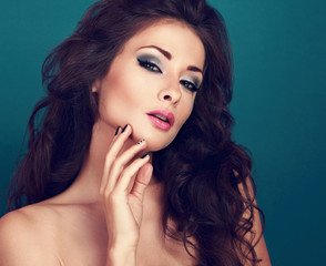 Beautiful fashionable makeup woman with bright eyeshadow, pink lipstick and long lashes looking sexy. Long curly volume hair and creative manicured nails. CLoseup