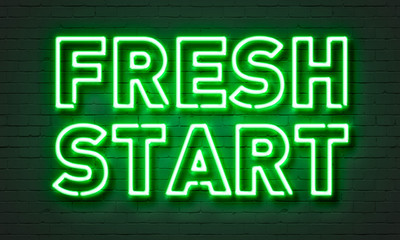 Fresh start neon sign on brick wall background.
