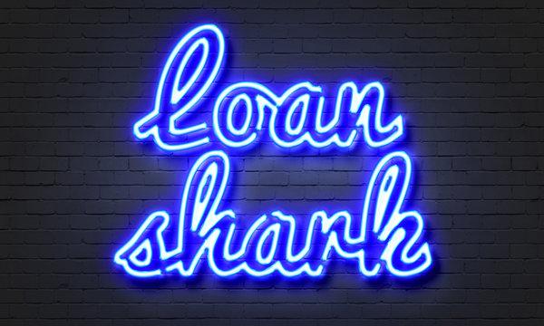 Loan shark neon sign on brick wall background.