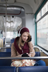 Beautiful young woman sitting in tram, listening to music and looking through window.