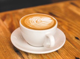 Perfect cappuccino in white cup on wood table