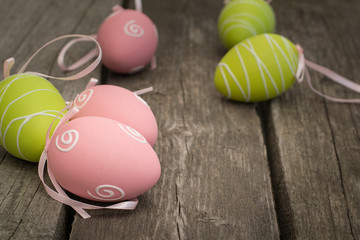 Painted easter eggs on wooden rustic board.  Selective focus, close up.