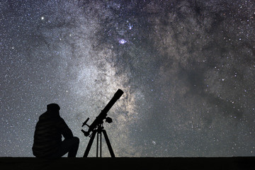 Man with astronomy  telescope looking at the stars. Wall mural