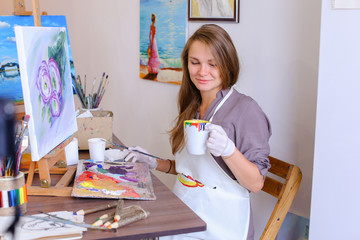 Cute Girl Artist Holds Brush in Hand And Draws, drinks from mug,