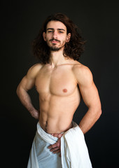 beautiful half naked guy with curly hair in a white drapery photo