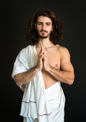 photo a man with curly hair in a white drapery folded his arms in prayer