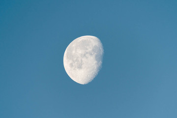 Waning moon in blue sky in early morning, showing detailed craters