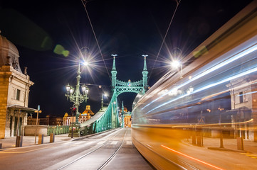 Night view of tram on Liberty Bridge or Freedom Bridge with lens flares in Budapest, Hungary
