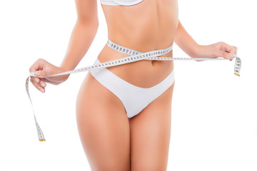 Close up of slim woman measuring her waist's size with tape measure