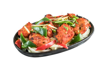 Chicken tikka kebab grilled in tandoor served on metal wooden plate isolated from background
