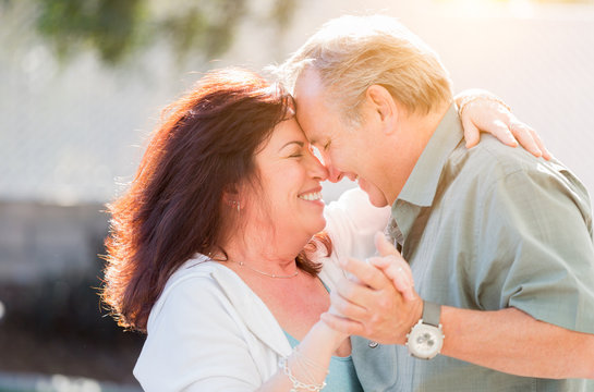 Happy Middle Aged Couple Enjoy A Romantic Slow Dance Outside.