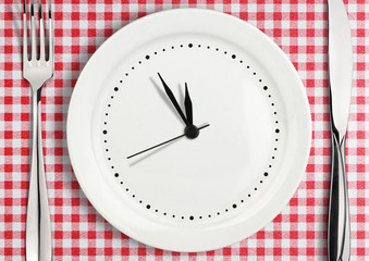 Table setting with blank clock on plate,  time concept