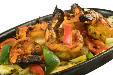 Indian starter meal tava tiger prawn grilled in tandoor and sizzling on wooden metal plate isolated from background