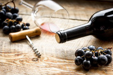 Glass of red wine and bottle with grape on wooden background