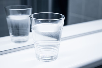 Glass of water stand near the mirror