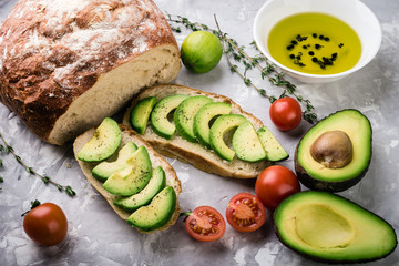 ciabatta with sliced avocado, tomatoes and herbs,  healthy food background