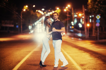 young couple dancing on the road.