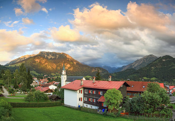 Wall Mural - Beautiful mountain village in evening ambience. Splendid sunset and alpenglow.