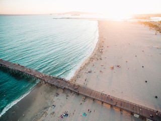 Aerial view of pier in sea with sandy beach at sunset