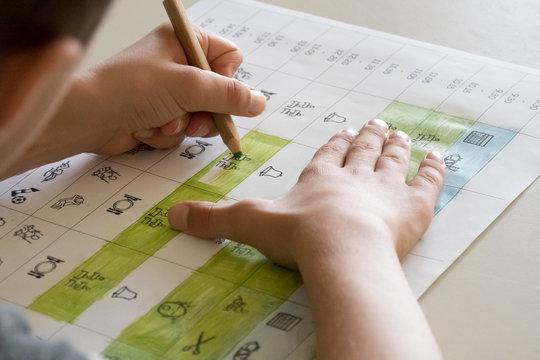 Ein Schüler malt einen Stundenplan mit Symbolen an