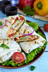 shawarma Lavash with chicken, tomatoes, lettuce and peppers on a blue background